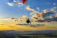 Paraglider flying against the setting sun & scattered clouds, above the South Downs National Park. Brighton, East Sussex. Uk.