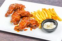 Hot and spicy buffalo chicken wings and crispy french fries with white sauce.
