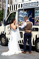Newly married couple enjoying a 99 ice cream cone on Liverpool seafront. England UK.