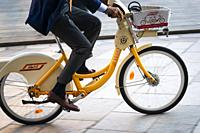 Italy, Lombardy, Milan, Businessmen Riding on a Rental Bike. .