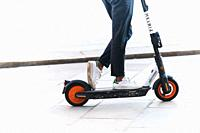 Italy, Lombardy, Milan, Woman Riding Electric Scooter. . . .