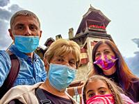 Family wearing masks visiting italian mountain town.