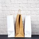 white and brown paper bags with handles on white brick wall background, environmental material, zero waste.