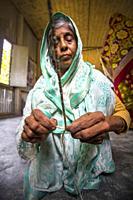 An old age woman is making on some fiber rope using on the banana tree fiber at Madhupur, Tangail, Bangladesh.