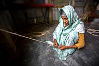 An old age woman is making a rope from the banana tree fibers in her skinny hands at Madhupur, Tangail, Bangladesh.