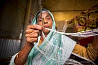 An old age woman is making on his skinny hands a rope from the banana tree fiber at Madhupur, Tangail, Bangladesh.
