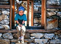 Young Sherpa Girl with Bandana Headband Sits on the window frame of under construction house and smiles at the camera in remote Manaslu region of Nepa...