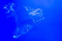 Transparent plastic bags floating underwater in blue ocean sea water, pollution by non-biodegradable plastic waste, hazard for marine wildlife
