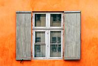 Old wooden window shutters of an european house with orange painted facade, vintage background.