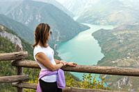 Woman hiker at mountain viewpoint enjoying the view of a lake and canyon.