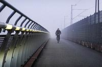 Stockholm, Sweden A bicyclist on the Arat bridge in the morning fog.