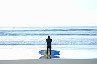 A male surfer contemplating the ocean in La Jolla, California.