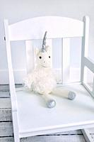Plush unicorn toy on a child's rocking chair.