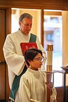A young robed boy altar assistant holds a ceremonial candle while waiting to participate in a procession to mass along with a book carrying deacon dur...