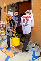 A Vietnamese American priest officiates as Hispanic and Caucasian charity clients carry food from the free pantry of a Southern California Catholic ch...