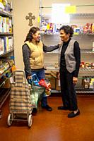 A Hispanic client at the charity food pantry of a Southern California Catholic church greets an African American church volunteer. Note cross on wall.