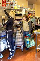 A Hispanic client at the charity food pantry of a Southern California Catholic church greets is assisted by a church volunteer.