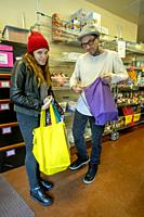 Clients at the charity food pantry of a Southern California Catholic church fill their shopping bags.
