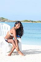 YOUNG African American WOMAN applying Sunscreen Lotion on legs at Caribbean Beach on the beach chair.