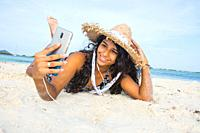 Young black woman taking a selfie at beach.