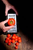 Conceptual A Man Hands Grinds Tomato On A Grater.