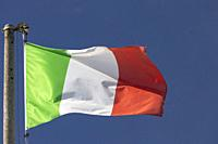 Italian flag blowing in the wind in the blue sky.