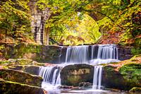 Autumn day in the sunny forest. Old stone bridge. Small river and several natural waterfalls.