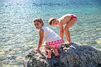 Young sister and brothet playing on a rock in front of a lake, smiling and enjoying outdoor life.