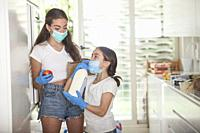 daughter and mom at home wearing masks and gloves because of the pandemia.
