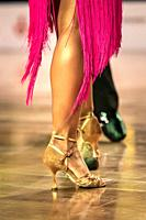 Beautiful womanish and masculine legs in active ballroom dance, indoors.