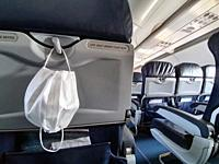 Protective medical white safety mask hanging in airplane for Covid-19, Travel and coronavirus concept close-up.
