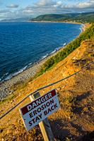 Danger sign on top of cliff along coastline at Pleasant Bay on the west coast of Cape Breton Island, Nova Scotia, Canada.