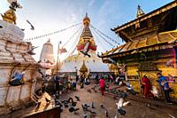 Wide view of Holy Swayambhunath Stupa early in the morning. People are offering prayers, pigeons flying by during sunrise. World Heritage Site.