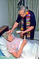 Catholic priest administers last rites to sick elderly femle in bed.