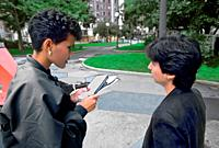 Black female newspaper, reporter interviews femal on the street feminist rights protester for newspaper.