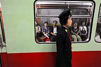 Pyongyang, North Korea, Asia - A platform attendant stands in front of a subway train of the Pyongyang Metro with waiting commuters at an underground ...