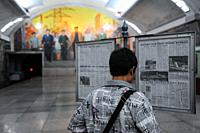 Pyongyang, North Korea, Asia - A commuter reads a publicly provided newspaper as he waits for the Pyongyang Metro on a station platform at a subway st...