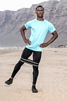 Full body focused black sportsman with hands on waist doing leg exercise with rubber band during fitness training on Famara Beach in Lanzarote, Spain.