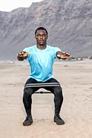 Full body serious African American sportsman squatting with rubber band during fitness workout on Famara Beach in Lanzarote, Spain.