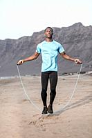 Full length African American male athlete jumping with rope on sandy Famara Beach during fitness workout in Lanzarote, Spain.