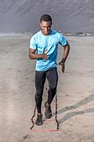 Full length concentrated African American athlete running on ladder during fitness workout on Famara Beach in Lanzarote, Spain.