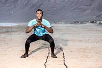 Full length serious black male athlete doing squats near ladder on sandy Famara Beach in Lanzarote, Spain.