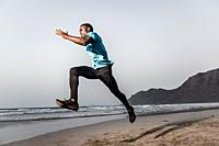 Full body serious ethnic sportsman leaping on sand near waving sea during fitness workout on Famara Beach in Lanzarote, Spain.