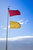 Yellow and red flags to highlight danger in the sea at the beach of Viareggio Tuscany Italy.