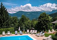 Sun loungers and swimming pool with mountain range in background, Alps, France, Europe.