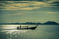 Longtail boat silhouette in waters by Railay, Krabi Province, Thailand, Asia.