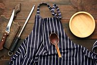 blue textile kitchen apron with white stripes and kitchen utensils, top view, brown wooden background.