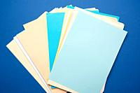 stack of multi-colored paper colored sheets on a blue background, top view.