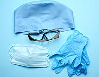 textile blue cap, disposable medical mask, pair of gloves and plastic glasses on a blue background, top view. Medic protective clothing.