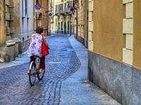 woman on a bicycle on a cobblestone street, Vercelli, Piedmont, Italy.